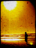 The Silhouette of an Adult Figure Walking on the Beach with a Setting Sun
