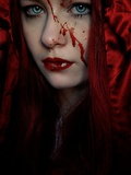 A Girl Wearing a Red Hood with Blood Splattered on Her Face