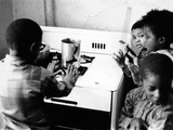 Four African American Children Cluster around the Gas Stove for Warmth