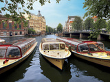 Refurbished Old Canal Cruise Boats Moored Along Amstel Canal in Amsterdam  the Netherlands