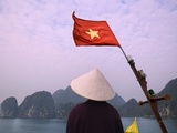 Girl with Conical Hat on a Junk Boat with National Flag and Karst Islands in Halong Bay  Vietnam
