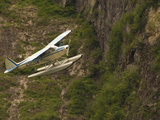 A Bush Pilot Flies His Float Plane Close to Mountain in Alaskan Canyon  USA