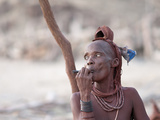 Himba Woman Smokes Outside Her Thatched Home in the Tiny Village  Purros  Namibia  Africa