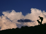A Hiker and Her Dog Below Thunderheads in Arid Volcanic Tablelands