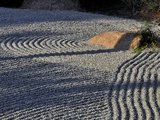 An Embedded Rock Catches the Afternoon Sun in a Raked Rock Garden