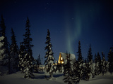Aurora Borealis over a Home in a Snowy Landscape with Evergreen Trees