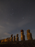 Moai Stand at Night Illuminated Beneath a Sky Full of Stars
