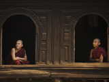 Monks Look Out from the Windows of a Wooden Monastery in Myanmar