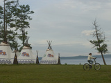 A Young Mongolian Rides Her Mountain Bike Past a Tourist Ger Camp at Toilogt