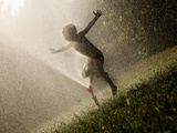 A Boy Plays in a Sprinkler on a Hot Summer Day