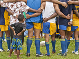 A Rugby Team in Huddle with a Child Watching Between Adults