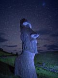 An Ancient Moai Statue on a Hillside at Night