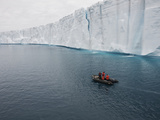 People in an Inflatable Boat Exploring an Ice Shelf