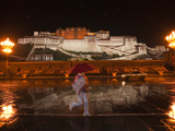 A Pedestrian in Front of the Potala Palace on a Rainy Night