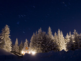 Stars in the Sky Above a House in a Snowy Forest