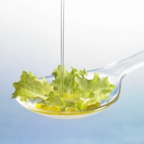 Oil Running onto Lettuce Leaf on Spoon