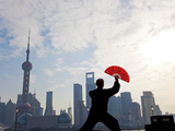 Practising Tai Chi with Fan  and Pudong Skyline  Early Morning  Shanghai  China