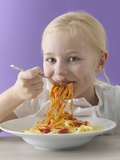Blond Girl Eating Spaghetti with Tomato Sauce