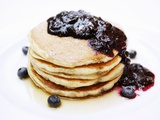 A Pile of Pancakes with Blueberry Sauce and Maple Syrup