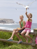 Two Girls Feeding Chips to a Seagull at the Beach