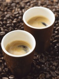Two Espressos Standing on Coffee Beans