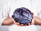 Man Holding a Red Cabbage in Both Hands