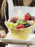 Waitress Serving a Basket of Fruit