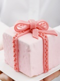 Hands Holding Cake with Marzipan Ribbon