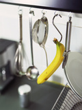 Banana and Kitchen Tools Hanging on Hooks in Kitchen
