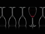 Row of Wine Glasses and a Glass of Red Wine Against a Black Background