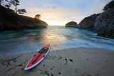 A Wave Washes Up China Cove at Sunset to a Stand Up Paddle Board