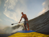 A Man Stand Up Paddleboard Surfing Waves