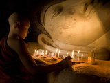A Novice Monk Lighting Candles at a Massive Buddha Statue in Burma (Myanmar)