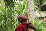 Schoolchild Embracing Tree Trunk and Looking Up  Bujumbura  Burundi