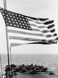 US Flag Waving in Foreground over Flight Deck of an Escort Carrier  July 16  1943