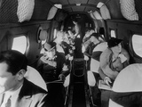 Stylishly Dressed Passengers Seated in a Commercial Flight in the 1930s