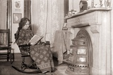 In a Heavy Robe  a Woman Reads in Front of a Coal Stove Installed in Her Fireplace