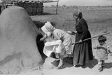 Spanish-American Women Placing Bread in Earthen Oven  New Mexico  1930s