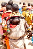 A Samburu Baby Rests On His Mother As She Dances with Others