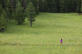 A Woman Trail Running in a Field