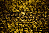 Cobblestones Reflecting Golden Light From Streetlights At Night