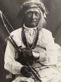 An Old War Chief  Seated On a Chair  Poses with a Bow and Arrows