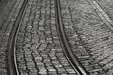 A Railway Tracks Running Through a Cobblestone Street