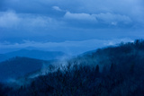 Pre-dawn Light Casts a Blue Hue Over Forested Mountains and Clouds