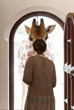 A Woman Greets a Rothschild Giraffe at the Door of a Lodge