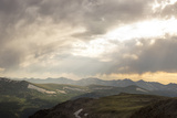 Sunlight Streaming Through Heavy Storm Clouds Over Mountains