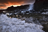 A Waterfall Cascades Into a Frozen River at Sunset