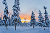 Orange Sky at Sunset Over Snow-covered Evergreens and a Tee Pee Form