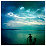 An Eight Year Old Boy Stands on a Dock on Sebago Lake at Sunset