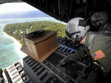 Airmen Push Out a Pallet of Donated Goods Over the Island of Yap from a C-130 Hercules